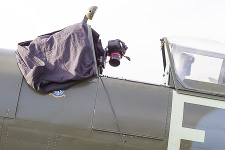 The photo shows the Spitfire cockpit area from the side, with the camera for the panoramic photography. The windscreen is covered by black tarpaulin to shield against the low morning sun.
