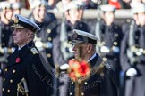 The golden cross with the poppies carried by the cross bearer, out of focus, and HRH the Duke of Edinburgh and HRH The Duke of York.