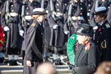 Commander Anne Sullivan, Royal Navy, handing, as Equerry, the wreath to HRH The Princess Royal. In the foreground, and out of focus, HM The Queen.