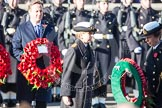 Commander Anne Sullivan, Royal Navy, handing, as Equerry, the wreath to HRH The Princess Royal. In the background the Prime Minister, David Cameron.