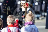 HRH Prince Michael of Kent about to lay his wreath at the Cenotaph. He is out of focus behind the golden cross with the red poppies held by the cross bearer.