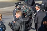 Remembrance Sunday at the Cenotaph in London 2014: After the March Past (see March Pastimage library): The stedycam operator for the BBC after carrying the 30kg camera during the complete March Past. Press stand opposite the Foreign Office building, Whitehall, London SW1, London, Greater London, United Kingdom, on 09 November 2014 at 12:24, image #316