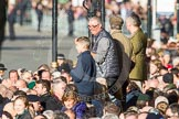 Remembrance Sunday at the Cenotaph in London 2014: Spectators on the eastern side of Whitehall waiting for the barriers to be removed.. Press stand opposite the Foreign Office building, Whitehall, London SW1, London, Greater London, United Kingdom, on 09 November 2014 at 12:24, image #319