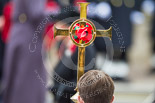 Remembrance Sunday at the Cenotaph 2015: Close-up of the Cross, with HM The Queen out of focus behind. Image #137, 08 November 2015 10:59 Whitehall, London, UK