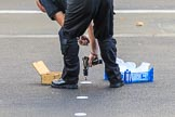 An Foreign and Commonwealth Office workman is screwing white discs onto the tarmac at Whitehall to mark the position of the members of the Royal Family and their Equerries before the  Remembrance Sunday Cenotaph Ceremony 2018 at Horse Guards Parade, Westminster, London, 11 November 2018, 08:54.