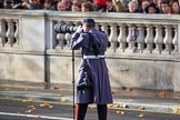 An army photographer shooting the service detachments arriving on Whitehall before the Remembrance Sunday Cenotaph Ceremony 2018 at Horse Guards Parade, Westminster, London, 11 November 2018, 10:23.