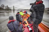 A press launch on the River Thames approaching Hammersmith Bridge, following the Cambridge University Boat Club Blue Boat.