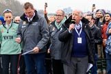 The Cancer Research UK Women's Boat Race 2018: Race umpire Sir Matthew Pinsent at the toss. On the left Cambridge stroke Olivia Coffey, and , with the microphone, for the BBC sports broadcaster David Mercer. River Thames between Putney Bridge and Mortlake, London SW15,  United Kingdom, on 24 March 2018 at 14:40, image #34