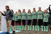 The Cancer Research UK Women's Boat Race 2018: The toss for the Women's Boat Race reserve boats, here, almost hidden, CUWBC president, and 5 seat Daphne Martschenko, then 2 seat Emma Andrews, 3 Anne Beenken, 4 Laura Foster, 6 Larkin Sayre, 7 Lucy Pike, stroke Millie Perrin, cox Sophie Wrixon. River Thames between Putney Bridge and Mortlake, London SW15,  United Kingdom, on 24 March 2018 at 14:55, image #69