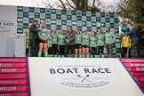 The Cancer Research UK Women's Boat Race 2018: The Women's Boat race trophy presentation - BBC Sport commentator Jason Mohammad, Myriam Goudet-Boukhatmi, Sophie Shapter, Olivia Coffey, Alice White, Boat Race Company director Fergus Murison, behind him Paula Wesselmann, then Thea Zabell, Kelsey Barolak, Imogen Grant, Tricia Smith, and CUWBC Head Coach Rob Baker. River Thames between Putney Bridge and Mortlake, London SW15,  United Kingdom, on 24 March 2018 at 17:07, image #268