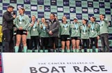 The Cancer Research UK Women's Boat Race 2018: The Women's Boat race trophy presentation - BBC Sport commentator Jason Mohammad, Myriam Goudet-Boukhatmi, Sophie Shapter, Olivia Coffey, Alice White, Boat Race Company director Fergus Murison, behind him Paula Wesselmann, then Thea Zabell, Kelsey Barolak, Imogen Grant, Tricia Smith, and CUWBC Head Coach Rob Baker. River Thames between Putney Bridge and Mortlake, London SW15,  United Kingdom, on 24 March 2018 at 17:08, image #270