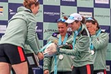The Cancer Research UK Women's Boat Race 2018: Cambridge 7 seat Myriam Goudet-Boukhatmi ho;ding the Women's Boat Race trophy, and cox Sophie Shapter filling it with champagne. River Thames between Putney Bridge and Mortlake, London SW15,  United Kingdom, on 24 March 2018 at 17:09, image #288