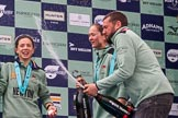The Cancer Research UK Women's Boat Race 2018: CUWBC Head Coach Rob Baker spraying Chapel Down Brut, On the left Imogen Grant, and next to Rob Tricia Smith. River Thames between Putney Bridge and Mortlake, London SW15,  United Kingdom, on 24 March 2018 at 17:09, image #293