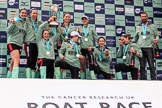 The Cancer Research UK Women's Boat Race 2018: The Cambridge women on the podium, with the Women's Boat Race trophy, their medals, lots of Castle Down Brut, and Cambridge head coach Rob Baker: Myriam Goudet-Boukhatmi, Olivia Coffey, Alice White, Paula Wesselmann, The Zabell, Sophie Shapter, Kelsey Barolak , Imogen Grant, and Tricia Smith. River Thames between Putney Bridge and Mortlake, London SW15,  United Kingdom, on 24 March 2018 at 17:10, image #300