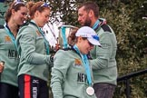 The Cancer Research UK Women's Boat Race 2018: Thea Zabell, Alice White, and Sophie Shapter leaving the podium, all still wet after spraying lots of Castle Down Brut. On the right, with the Boat Race trophy, Vambridge Head coach Rob Baker. River Thames between Putney Bridge and Mortlake, London SW15,  United Kingdom, on 24 March 2018 at 17:10, image #304