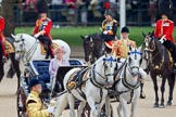 Trooping the Colour 2010: Her Majesty The Queen, sitting in her Ivory Mounted Phaeton,  inspecting the line of soldiers on the parade ground.  Following the carriage the Royal Colonels, Prince Charles (cut off at the very left), the Duke of Kent, and the Princess Royal.  In the background spectators watching from St. James's Park, on the western end of the parade ground, and in the foreground one of the Drum Majors.. Horse Guards Parade, Westminster, London SW1, Greater London, United Kingdom, on 12 June 2010 at 11:06, image #91