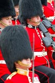 Trooping the Colour 2011: Young guardsmen from No. 1 Guard, 1st Battalion Scots Guards, the Escort for the Colour, marching. The guardsman in the middle is wearing his Afghanistan Service Medal. In front, and out of focus, Major Roderick Shannon, commanding the Escort.. Horse Guards Parade, Westminster, London SW1, Greater London, United Kingdom, on 11 June 2011 at 11:36, image #235