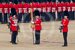 Trooping the Colour 2011: The Sergeant of the Ecort to the Colour, Colour Sergeant Chris Millin, holding the flag, whilst the two sentries present arms, and the Duty Drummer, holding the colour case, salutes. Image #57, 11 June 2011 10:33 Horse Guards Parade, London, UK