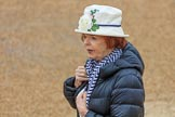 Female spectator, wearing a white hat with a large white rose in front, before The Colonel's Review 2018 (final rehearsal for Trooping the Colour, The Queen's Birthday Parade)  at Horse Guards Parade, Westminster, London, 2 June 2018, 09:07.