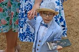 Young boy, wearing a striped three-piece-suit with a bow tie and a hat, holding a paper copy of the programme before The Colonel's Review 2018 (final rehearsal for Trooping the Colour, The Queen's Birthday Parade)  at Horse Guards Parade, Westminster, London, 2 June 2018, 09:13.