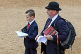 Father and son, both in dark suits, and the father with a Household Division tie, holding their printed tickets and an event programme before The Colonel's Review 2018 (final rehearsal for Trooping the Colour, The Queen's Birthday Parade)  at Horse Guards Parade, Westminster, London, 2 June 2018, 09:19.
