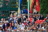 Spectators on the A grandstand, with the Band of the Welsh Guards in the background, turning from The Mall to Horse Guards Parade during The Colonel's Review 2018 (final rehearsal for Trooping the Colour, The Queen's Birthday Parade)  at Horse Guards Parade, Westminster, London, 2 June 2018, 10:10.