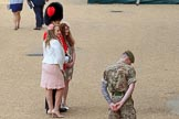 Two young ladies, wearing fascinators, posing with Coldstream Guards officer for a photo before Trooping the Colour 2018, The Queen's Birthday Parade at Horse Guards Parade, Westminster, London, 9 June 2018, 09:02.
